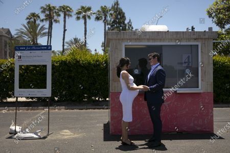 Stock Photo of Jeffery Baker and Shannon Carney, who is eight months pregnant, exchange vows during their marriage service in the parking lot of the Honda Center in Anaheim, Calif., . The coronavirus pandemic disrupted people from tying the knot, but not for long. The Orange County Clerk Recorder's office has set up wedding booths in the parking lot of Honda Center, home of the NHL's Anaheim Ducks, to resume its marriage services. Started in mid-April, the pop-up site has been serving more than 100 couples a day. One witness for each couple is allowed while the rest of wedding guests are asked to stay in their cars