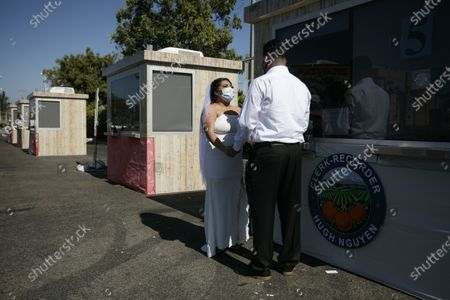Stock Image of Ramon Rodriguez and Bianney Rodriguez exchange vows during their marriage service in the parking lot of the Honda Center in Anaheim, Calif., . The coronavirus pandemic disrupted people from tying the knot, but not for long. The Orange County Clerk Recorder's office has set up wedding booths in the parking lot of Honda Center, home of the NHL's Anaheim Ducks, to resume its marriage services. Started in mid-April, the pop-up site has been serving more than 100 couples a day. One witness for each couple is allowed while the rest of wedding guests are asked to stay in their cars