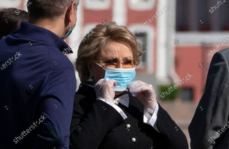 Federation Council Speaker Valentina Matviyenko, centre, corrects her face mask to protect against coronavirus after a flower tribute laying ceremony during the celebration of the 317th anniversary of St. Petersburg in St.Petersburg, Russia