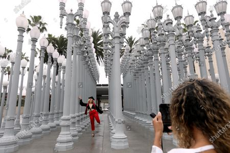 Manon Guijarro, 21, who just graduated from Pierce College, has her personal graduation photo made by friend Paige Johnson, 21, at Chris Burden's outdoor, 'Urban Light,' at the Los Angeles County Museum of Art. Some outdoor museums can open but LACMA's indoors is still closed but outdoor exhibits are still open to the public. Outdoor museums are among the places that Gov. Gavin Newsom said Tuesday have the green light to reopen in some regions, but that statement has created confusion is places such as Los Angeles County, which is giving museums, outdoor and otherwise, a red light for now.