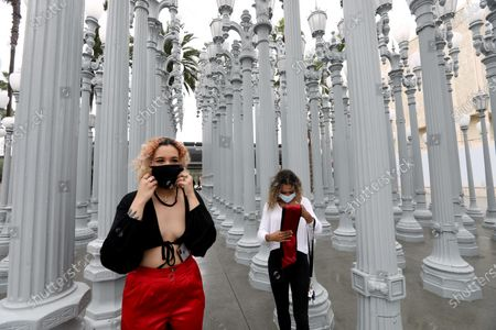 Manon Guijarro, 21, left, who just graduated from Pierce College, puts on her mask after her friend Paige Johnson, 21, finished taking her personal graduation photo at Chris Burden's outdoor, 'Urban Light,' at the Los Angeles County Museum of Art. Some outdoor museums can open but LACMA's indoors is still closed but outdoor exhibits are still open to the public. Outdoor museums are among the places that Gov. Gavin Newsom said Tuesday have the green light to reopen in some regions, but that statement has created confusion is places such as Los Angeles County, which is giving museums, outdoor and otherwise, a red light for now.