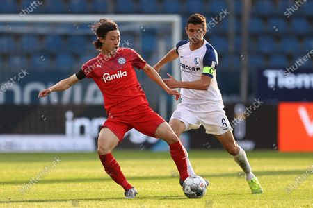 Lee Jae-sung (L) of Holstein Kiel battles for the ball with Anthony Losilla of VfL Bochum during the German Second Bundesliga division match between VfL Bochum 1848 and Holstein Kiel at Vonovia Ruhrstadion in Bochum, Germany, 27 May 2020.