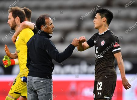Stock Image of Jos Luhukay (L) head coach of St. Pauli fist bumps Ryo Miyaichi of St. Pauli after the German Bundesliga Second Division soccer match between FC St. Pauli and 1. FC Heidenheim 1846 at Millerntor Stadium in Hamburg, Germany, 27 May 2020.