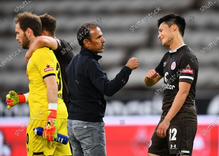 Stock Picture of Jos Luhukay (L) head coach of St. Pauli fist bumps Ryo Miyaichi of St. Pauli after the German Bundesliga Second Division soccer match between FC St. Pauli and 1. FC Heidenheim 1846 at Millerntor Stadium in Hamburg, Germany, 27 May 2020.