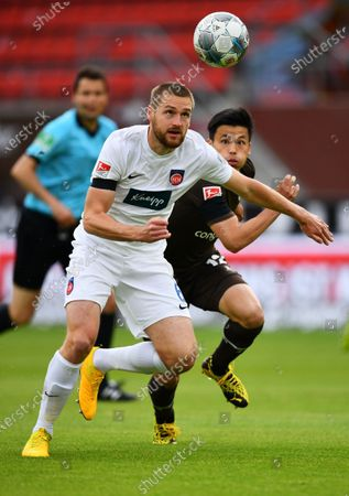 Patrick Mainka (L) of 1.FC Heidenheim is challenged by Ryo Miyaichi of St. Pauli during the German Bundesliga Second Division soccer match between FC St. Pauli and 1. FC Heidenheim 1846 at Millerntor Stadium in Hamburg, Germany, 27 May 2020.