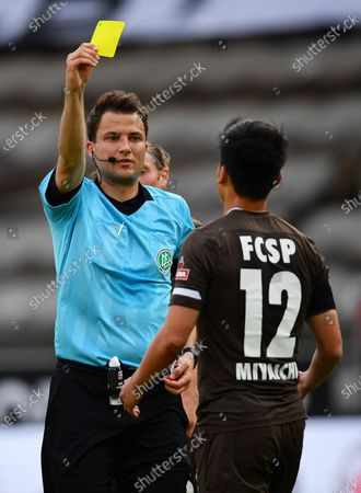 Referee Lass Koslowski gives Ryo Miyaichi of St. Pauli a yellow card during the German Bundesliga Second Division soccer match between FC St. Pauli and 1. FC Heidenheim 1846 at Millerntor Stadium in Hamburg, Germany, 27 May 2020.