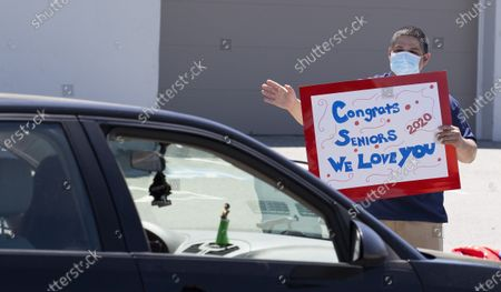 A teacher holds a sign reading 'Congrats Seniors 2020 We Love You' as graduates drive past during a high school senior class parade outside of Central Catholic High School in Lawrence, Massachusetts, USA, 27 May 2020. With the remainder of the school year cancelled on 21 April 2020 to help stop the spread of the coronavirus and Covid-19, many schools have held alternative celebrations for the graduating seniors of the Class of 2020.