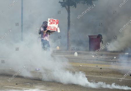 A protester stands as teargas is released by police as protesters clash with officers outside a Minneapolis police precinct two days after George Floyd died while in police custody, in Minneapolis, Minnesota USA, 27 May 2020. A bystander's video posted online on 25 May appeared to show George Floyd, 46, pleading with arresting officers that he couldn't breathe as an officer knelt on his neck. The unarmed black man later died in police custody.