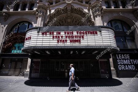 A man wearing a face mask walks past the Million Dollar Theater which front reads 'We're In This Together, Stay Positive, Stay Home', amid the coronavirus pandemic in Los Angeles, California, USA, 27 May 2020. Los Angeles County officials have announced on 26 May, moving forward with the reopening of the County, with restaurants allowed to open with restrictions.