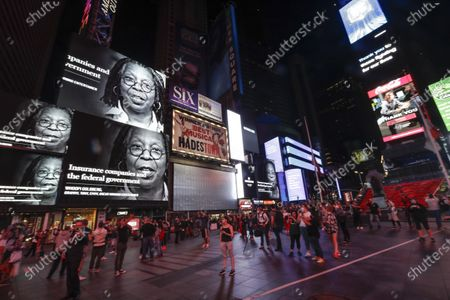 People wear protective masks during the coronavirus pandemic while watching Whoopi Goldberg on a billboard for a call to support restaurants, hospitality businesses and nonprofits, in New York