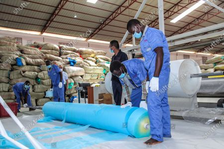 Employees work at Lida Packaging Products Limited in Mukono district, central Uganda, May 26, 2020.   Ugandan President Yoweri Museveni on Tuesday launched two production lines at a Chinese-owned factory making face masks to plug shortages as the country eased lockdown restrictions.