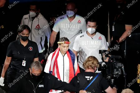 Stock Photo of Michelle Waterson, center, enters the arena surrounded by her team wearing masks because of the coronavirus pandemic during a UFC 249 mixed martial arts bout, in Jacksonville, Fla