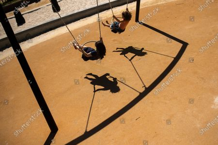 Children sway on a swing in a playground at Leopold park during the partial lifting of coronavirus, COVID-19, lockdown regulations in Brussels
