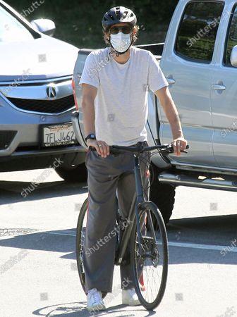 Sacha Baron Cohen riding his bike braving the inclines roads