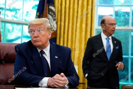 President Donald Trump listens as he receives a briefing on the 2020 hurricane season in the Oval Office of the White House, in Washington. At right is Commerce Secretary Wilbur Ross