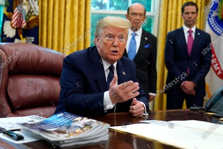 President Donald Trump speaks as he receives a briefing on the 2020 hurricane season in the Oval Office of the White House, in Washington. Watching are Commerce Secretary Wilbur Ross and Neil Jacobs, assistant Secretary of Commerce for Environmental Observation and Prediction