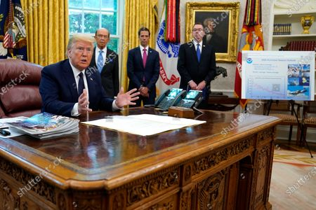 President Donald Trump speaks as he receives a briefing on the 2020 hurricane season in the Oval Office of the White House, in Washington. Watching are Commerce Secretary Wilbur Ross and Neil Jacobs, assistant Secretary of Commerce for Environmental Observation and Prediction, and Pete Gaynor, administrator of the Federal Emergency Management Agency