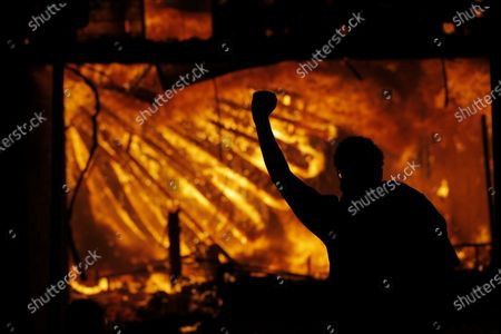 Protester gestures in front of the burning 3rd Precinct building of the Minneapolis Police Department, in Minneapolis. Protests over the death of George Floyd, a black man who died in police custody Monday, broke out in Minneapolis for a third straight night