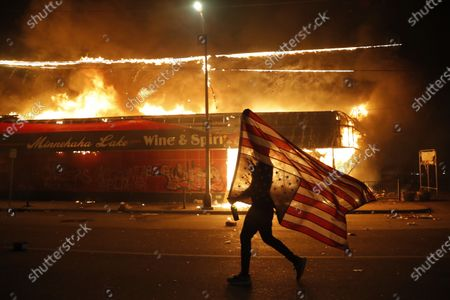 Protester carries the carries a U.S. flag upside, a sign of distress, next to a burning building, in Minneapolis. Protests over the death of George Floyd, a black man who died in police custody Monday, broke out in Minneapolis for a third straight night