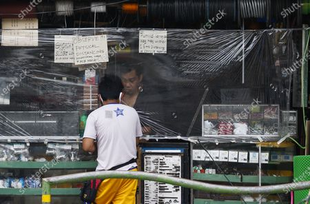 A plastic sheet separates a vendor from a customer as protection from potential Covid-19 transmission at a hardware store in Quezon City, Metro Manila, Philippines 26 May 2020 (issued 29 May 2020). On the way to the longest confinement worldwide due to the Covid-19 pandemic, Manila reaches 76 days in strict quarantine, a mark so far only reached by the Chinese city of Wuhan which was the epicenter of the outbreak. The excessive confinement alone has proven to be ineffective to curb the coronavirus.