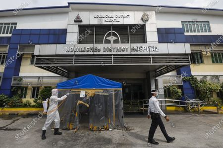 A maintenance worker (L) disinfects areas outside a hospital in Quezon City, Metro Manila, Philippines 26 May 2020 (issued 29 May 2020). On the way to the longest confinement worldwide due to the Covid-19 pandemic, Manila reaches 76 days in strict quarantine, a mark so far only reached by the Chinese city of Wuhan which was the epicenter of the outbreak. The excessive confinement alone has proven to be ineffective to curb the coronavirus.