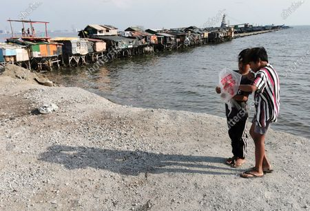 Filipino children hold a kite during a coronavirus pandemic at a slum area in Manila, Philippines, 27 May 2020 (issued on 29 May 2020). On the way to the longest confinement worldwide due to COVID-19 pandemic, Manila reaches 76 days in strict quarantine, a mark so far only reached by the Chinese city of Wuhan - epicenter of the outbreak -, an excessive confinement that has proven to be alone ineffective to curb coronavirus.