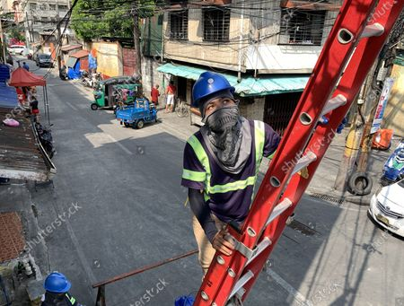 A Filipino laborer installs electric cables during a coronavirus pandemic at a slum area in Manila, Philippines, 27 May 2020 (issued on 29 May 2020). On the way to the longest confinement worldwide due to COVID-19 pandemic, Manila reaches 76 days in strict quarantine, a mark so far only reached by the Chinese city of Wuhan - epicenter of the outbreak -, an excessive confinement that has proven to be alone ineffective to curb coronavirus.