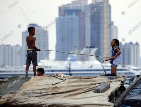 A Filipino boy uses a stick to employ social distancing during a coronavirus pandemic at a slum area in Manila, Philippines, 27 May 2020 (issued on 29 May 2020). On the way to the longest confinement worldwide due to COVID-19 pandemic, Manila reaches 76 days in strict quarantine, a mark so far only reached by the Chinese city of Wuhan - epicenter of the outbreak -, an excessive confinement that has proven to be alone ineffective to curb coronavirus.