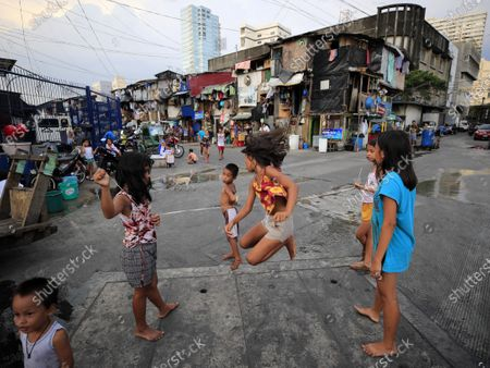 Filipino children play along a road during a coronavirus pandemic at a slum area in Manila, Philippines, 27 May 2020 (issued on 29 May 2020). On the way to the longest confinement worldwide due to COVID-19 pandemic, Manila reaches 76 days in strict quarantine, a mark so far only reached by the Chinese city of Wuhan - epicenter of the outbreak -, an excessive confinement that has proven to be alone ineffective to curb coronavirus.