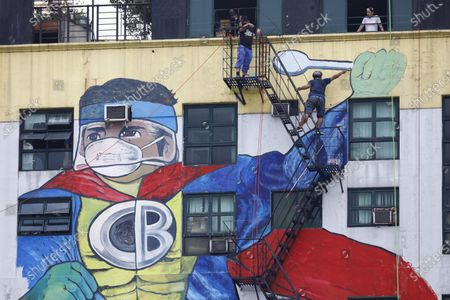 An artwork painted on a building by an artists' collective called Art Atak features local superhero character 'Captain Barbel' wearing a protective mask in tribute to frontline workers against Covid-19 in Quezon City, Metro Manila, Philippines, 27 May 2020 (issued 29 May 2020). On the way to the longest confinement worldwide due to the Covid-19 pandemic, Manila reaches 76 days in strict quarantine, a mark so far only reached by the Chinese city of Wuhan which was the epicenter of the outbreak. The excessive confinement alone has proven to be ineffective to curb the coronavirus.
