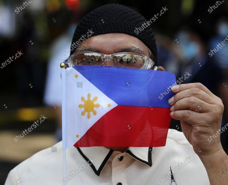 A Filipino government worker displays a flag during a coronavirus pandemic at a slum area in Manila, Philippines, 28 May 2020 (issued on 29 May 2020). On the way to the longest confinement worldwide due to COVID-19 pandemic, Manila reaches 76 days in strict quarantine, a mark so far only reached by the Chinese city of Wuhan - epicenter of the outbreak -, an excessive confinement that has proven to be alone ineffective to curb coronavirus.