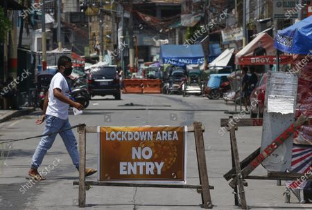 A resident crosses a street of a quarantined community in Caloocan City, Metro Manila, Philippines, 28 May 2020 (issued 29 May 2020). On the way to the longest confinement worldwide due to the Covid-19 pandemic, Manila reaches 76 days in strict quarantine, a mark so far only reached by the Chinese city of Wuhan which was the epicenter of the outbreak. The excessive confinement alone has proven to be ineffective to curb the coronavirus.