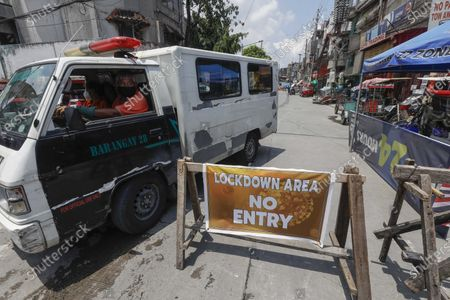 Emergency responders in a vehicle pass by a checkpoint of a quarantined community in Caloocan City, Metro Manila, Philippines, 28 May 2020 (issued 29 May 2020). On the way to the longest confinement worldwide due to the Covid-19 pandemic, Manila reaches 76 days in strict quarantine, a mark so far only reached by the Chinese city of Wuhan which was the epicenter of the outbreak. The excessive confinement alone has proven to be ineffective to curb the coronavirus.