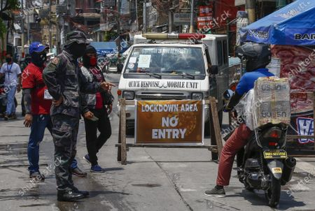 Stock Photo of A police officer (L) questions a delivery service worker (R) at a checkpoint of a quarantined community in Caloocan City, Metro Manila, Philippines, 28 May 2020 (issued 29 May 2020). On the way to the longest confinement worldwide due to the Covid-19 pandemic, Manila reaches 76 days in strict quarantine, a mark so far only reached by the Chinese city of Wuhan which was the epicenter of the outbreak. The excessive confinement alone has proven to be ineffective to curb the coronavirus.