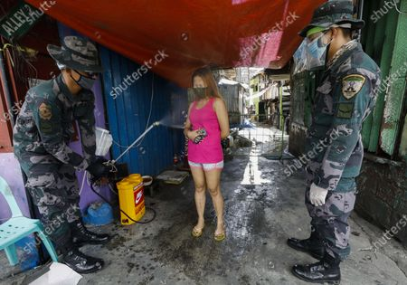 Stock Image of Philippine police spray disinfectant on a resident of a quarantined community in Quezon City, Metro Manila, Philippines, 28 May 2020 (issued 29 May 2020). On the way to the longest confinement worldwide due to the Covid-19 pandemic, Manila reaches 76 days in strict quarantine, a mark so far only reached by the Chinese city of Wuhan which was the epicenter of the outbreak. The excessive confinement alone has proven to be ineffective to curb the coronavirus.