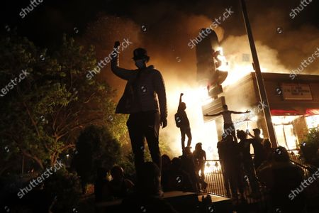 Protesters gather in front of a burning fast food restaurant, in Minneapolis. Protests over the death of George Floyd, a black man who died in police custody Monday, broke out in Minneapolis for a third straight night