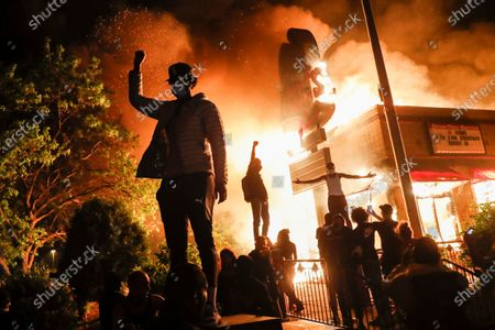 Protestors demonstrate outside of a burning fast food restaurant, in Minneapolis. Protests over the death of George Floyd, a black man who died in police custody Monday, broke out in Minneapolis for a third straight night