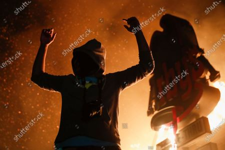 Protestor reacts beside a burning fast food restaurant near the Minneapolis 3rd Police Precinct, in Minneapolis. Protests over the death of George Floyd, a black man who died in police custody Monday, broke out in Minneapolis for a third straight night
