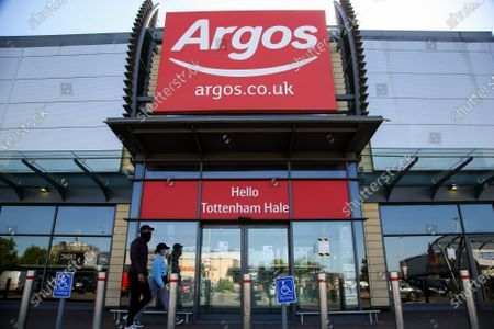 People wearing face coverings walk past Argos store in Tottenham Hale in north London. Prime Minister Boris Johnson has said that from 15 June all non-essential retailers, including shops selling clothes and indoor markets can open as lockdown restrictions are eased in England after ten weeks of the coronavirus lockdown.