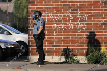 St. Paul Police officer looks on as protesters are pushed back by teargas, in St. Paul, Minn. Violent protests over the death of George Floyd, the black man in police custody broke out in Minneapolis for a second straight night Wednesday, with protesters in a standoff with officers outside a police precinct and looting of nearby stores