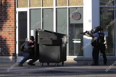 Protester, left, hides behind a dumpster he pulled as a barrier while St. Paul Police officers move in to retrieve the dumpster, in St. Paul, Minn. Violent protests over the death of George Floyd, the black man in police custody broke out in Minneapolis for a second straight night Wednesday, with protesters in a standoff with officers outside a police precinct and looting of nearby stores