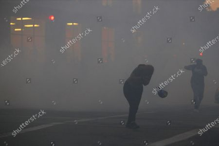 Protester loses her hat while reacting to teargas set off by St. Paul Police officers, in St. Paul, Minn. Violent protests over the death of George Floyd, the black man in police custody broke out in Minneapolis for a second straight night Wednesday, with protesters in a standoff with officers outside a police precinct and looting of nearby stores