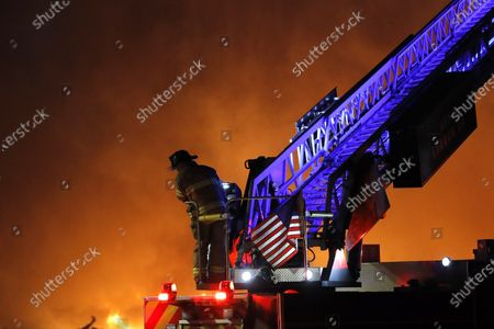 Firefighter stands on an engine while tending to a large structure fire, in St. Paul, Minn. Violent protests over the death of George Floyd, the black man in police custody broke out in Minneapolis for a second straight night Wednesday, with protesters in a standoff with officers outside a police precinct and looting of nearby stores