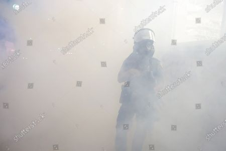 St. Paul Police officer walks among smoke after officers set off teargas on protesters, in St. Paul, Minn. Violent protests over the death of George Floyd, the black man in police custody broke out in Minneapolis for a second straight night Wednesday, with protesters in a standoff with officers outside a police precinct and looting of nearby stores
