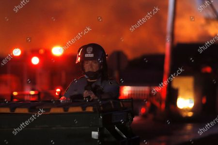 St. Paul Police officer stands guard behind a dumpster while guarding a building engulfed in flames, in St. Paul, Minn. Violent protests over the death of George Floyd, the black man in police custody broke out in Minneapolis for a second straight night Wednesday, with protesters in a standoff with officers outside a police precinct and looting of nearby stores