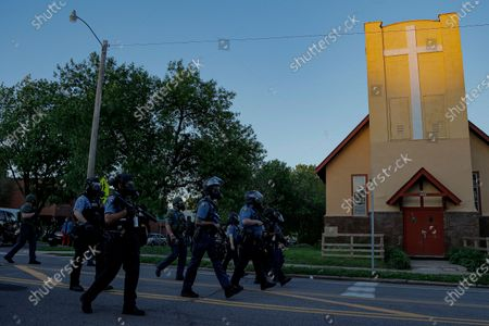 St. Paul Police officers move in on a crowd, in St. Paul, Minn. Violent protests over the death of George Floyd, the black man in police custody broke out in Minneapolis for a second straight night Wednesday, with protesters in a standoff with officers outside a police precinct and looting of nearby stores
