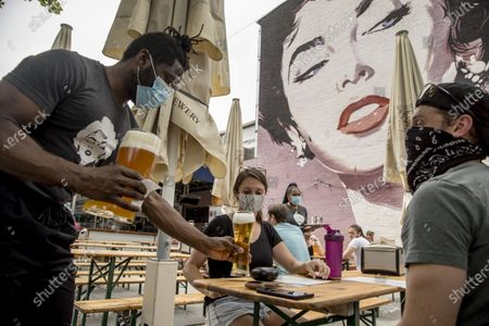Large Elizabeth Taylor mural is visible behind waiter Voltaires Max, left, as he serves beers to Bridgid McAndrew, center, and Nate Hubbard, right, at Dacha Beer Garden in the Shaw neighborhood in Washington, after the District of Columbia gradually loosens stay-at-home rules that have been in place since March 25 because of the pandemic and allows restaurants to resume outdoor dining