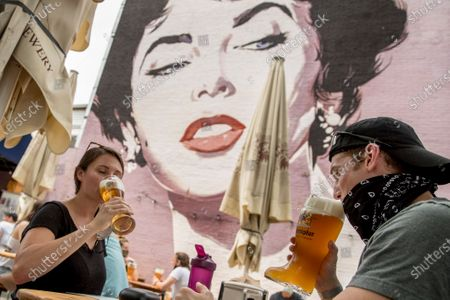 Stock Picture of Large Elizabeth Taylor mural is visible behind Bridgid McAndrew, left, and Nate Hubbard, right, drink beers at Dacha Beer Garden in the Shaw neighborhood in Washington, after the District of Columbia gradually loosens stay-at-home rules that have been in place since March 25 because of the pandemic and allows restaurants to resume outdoor dining
