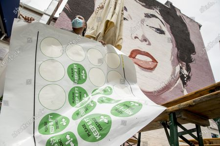 """Large Elizabeth Taylor mural is visible behind Kija Kennedy, left, as she helps put down social distancing stickers on the ground that read """"Please Keep 6 Ft. Distance"""" outside Dacha Beer Garden in the Shaw neighborhood in Washington, as the District of Columbia gradually loosens stay-at-home rules that have been in place since March 25 because of the pandemic and allows restaurants to resume outdoor dining"""
