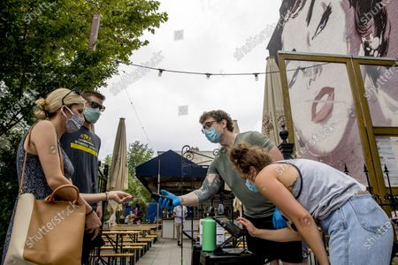 Stock Photo of Large Elizabeth Taylor mural is visible behind Steven Scammacca, center right, as he checks IDs and Amy Symonds as she works at Dacha Beer Garden which has opened in the Shaw neighborhood in Washington, as the District of Columbia gradually loosens stay-at-home rules that have been in place since March 25 because of the pandemic and allows restaurants to resume outdoor dining